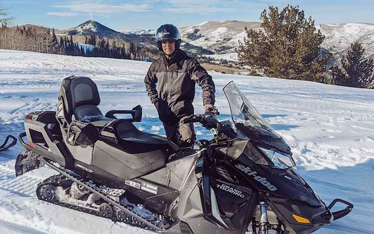 man standing next to a snowmobile on a snowy mountain in utah